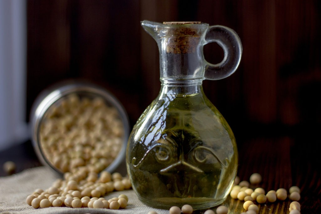 Natural soy bean oil with soybeans near it