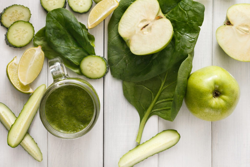 Detox cleanse drink, green smoothie ingredients. Natural, organic healthy juice in glass jar for weight loss diet or fasting day. Cucumber, apple, lime and spinach mix on white wood top view
