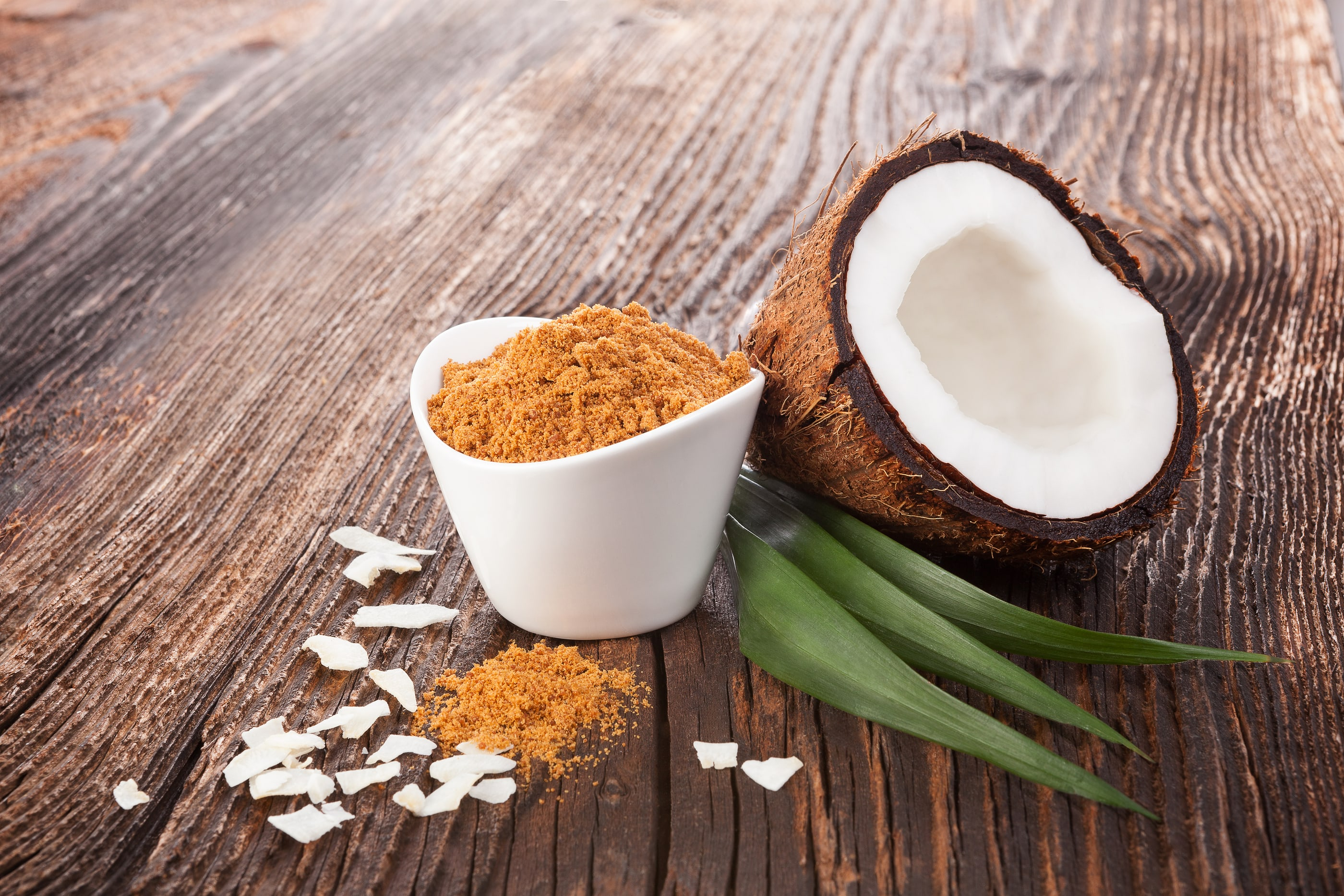 Coconut sugar and coconut on wooden table. Healthy sugar eating.