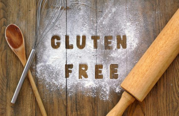 Gluten free flour with text gluten free in English language with wooden spoon beater and rolling pin on dark brown wooden backgroundfront horizontal view