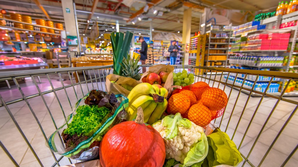 Grocery shop cart in supermarket filled up with fresh and healthy food products as seen from the customers point of view with people shopping in background