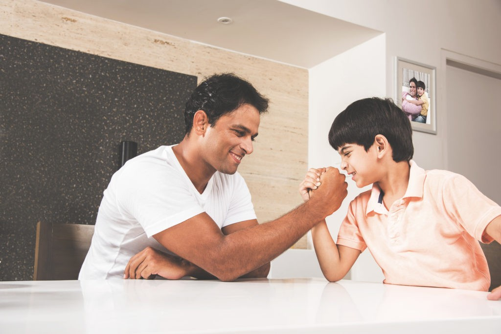 Family time - indian young father playing or competing in arm wrestle or wrestling with son at dining table