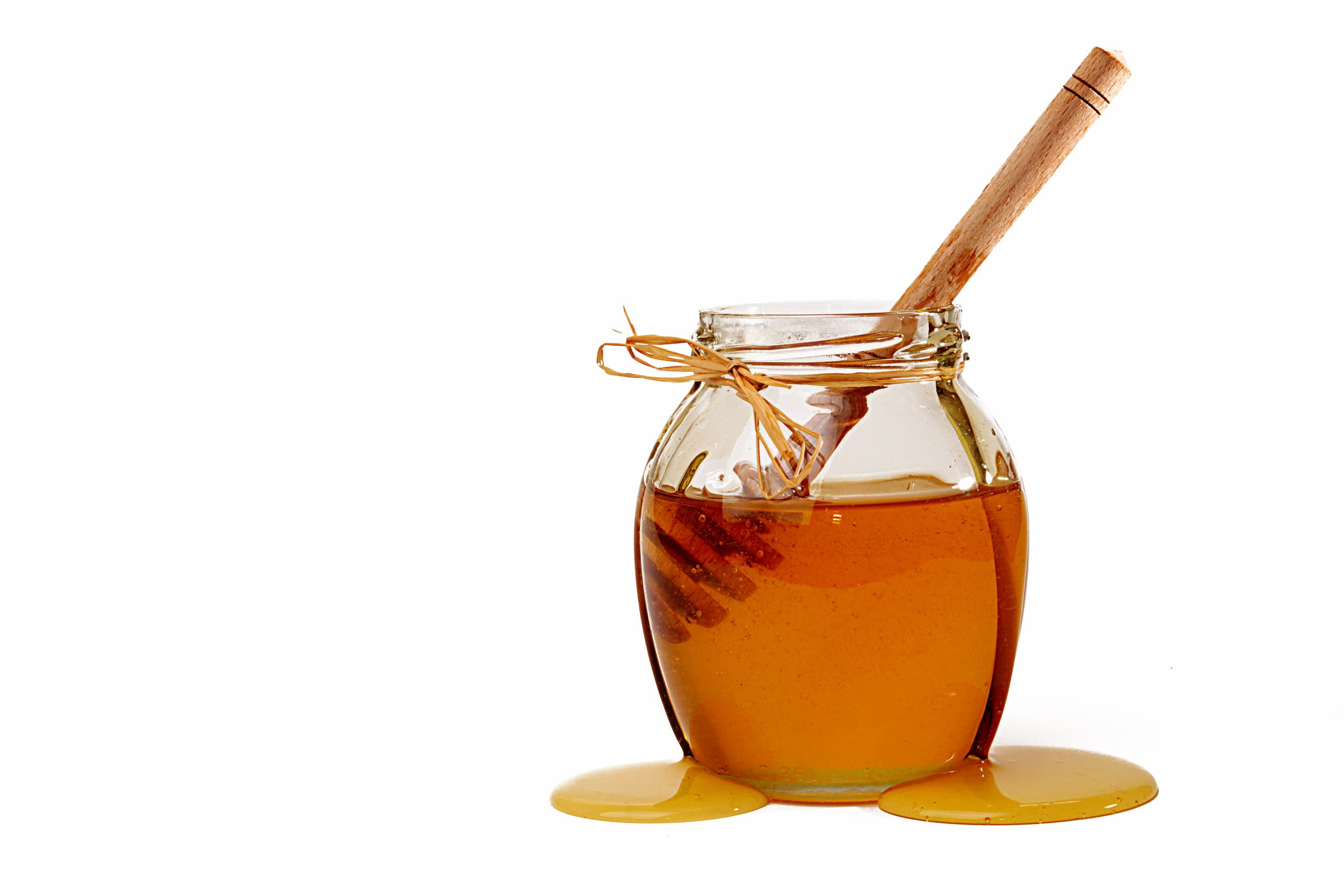 Delicious sweet honey in glass jar. Honey and dipper in jar on white background. Spread honey next to jar. Natural organic food concept