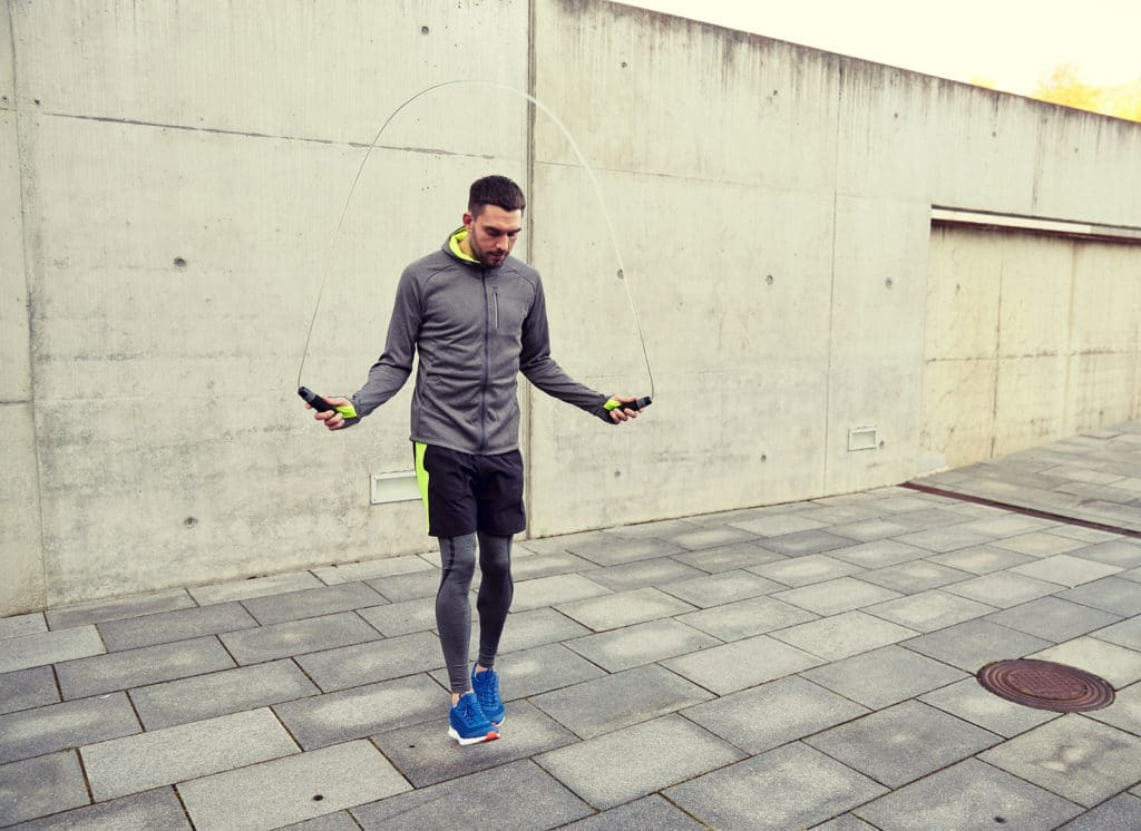 interval training, fitness, sport, people, exercising and lifestyle concept - man skipping with jump rope outdoors