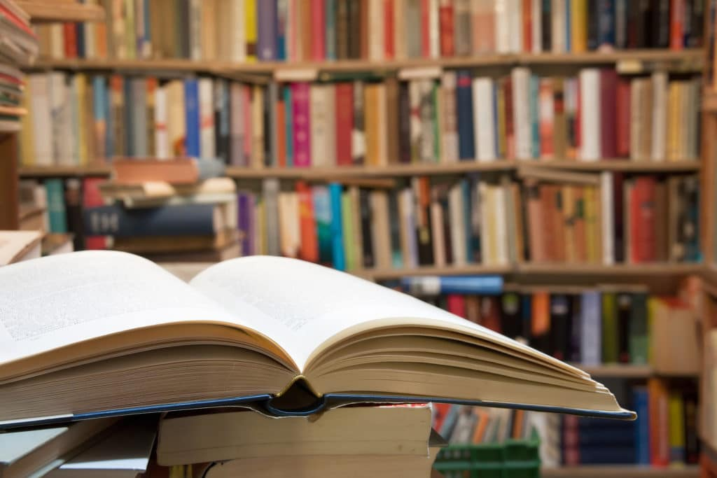 Old open book with a vintage library background