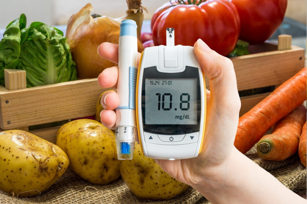 Hand holds glucometer for measuring glucose level. Vegetables in background. Diabetic diet and diabetes concept.