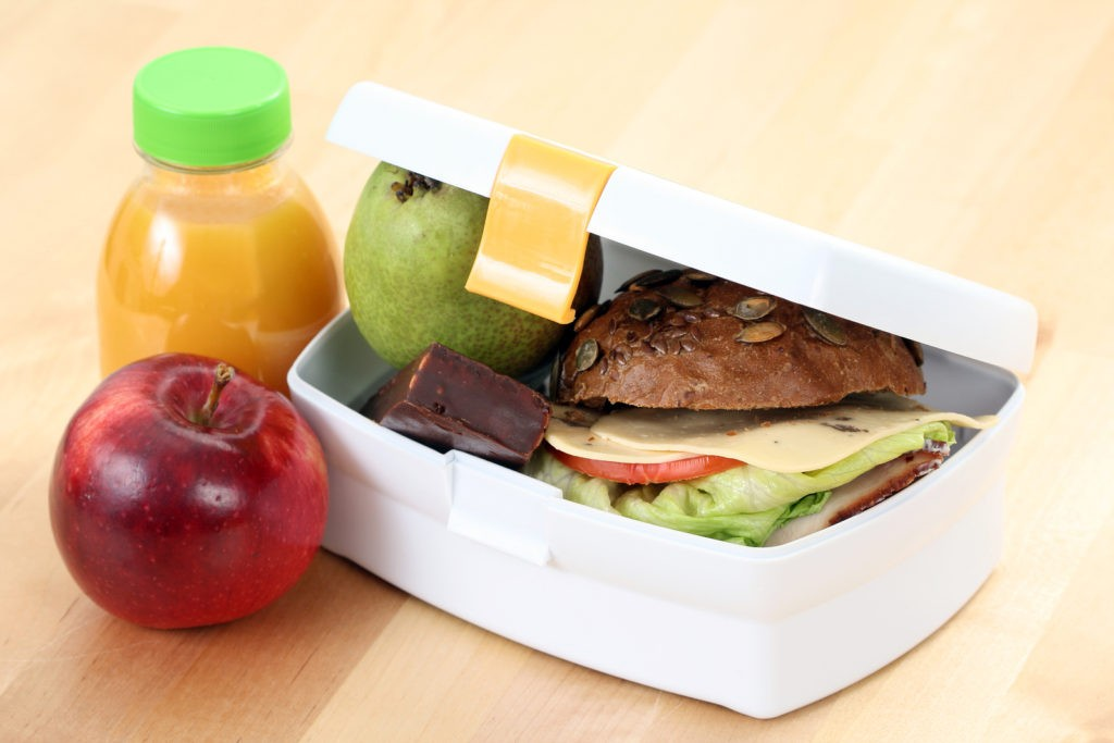 box with sandwich fruits and chocolate and bottle of juice