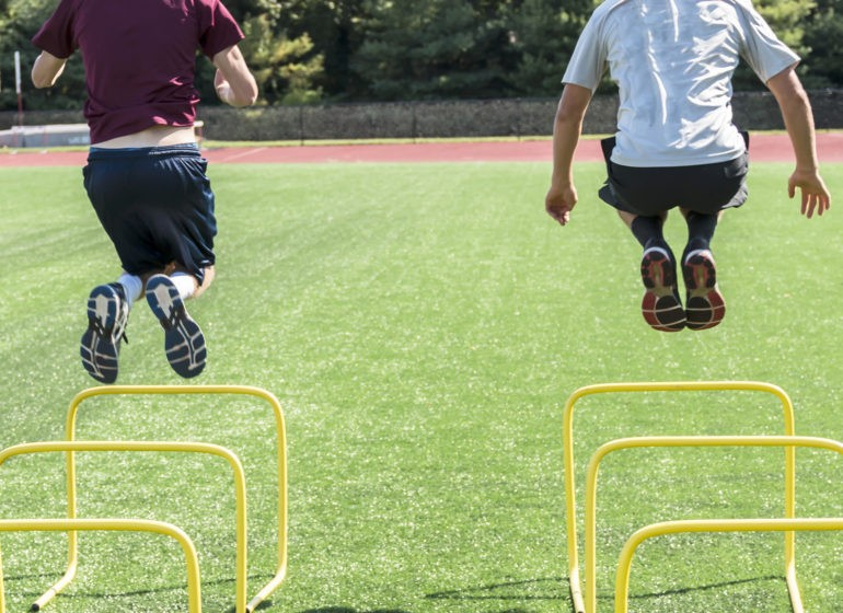 Two high school athletes bound over yellow hurdles on a green turf field during afternoon practice.