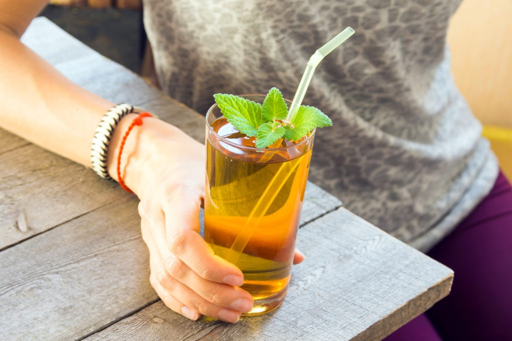 Woman (girl) drink Kombucha tea super food pro biotic beverage in glass with mint on wooden background copy space - homemade healthy organic fermented probiotic drink in female hand