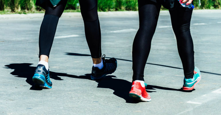 Legs of two women while exercising walking in a street